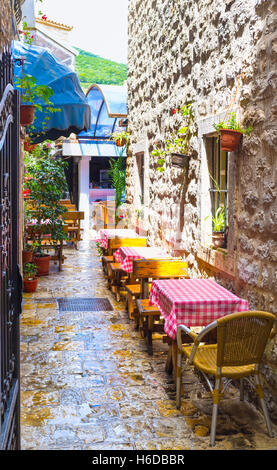 The street cafe located in the narrow lane in the old town of Budva, Montenegro. - Stock Photo