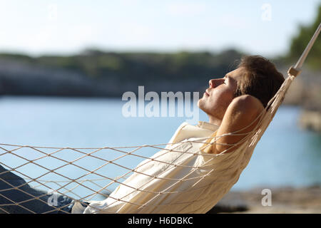 Side view of a casual happy man relaxing on a hammock in the beach on holidays