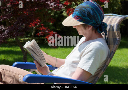 Someone retired senior woman relaxing in a backyard garden chair reading a book in summer sunshine shaded by sunhat. - Stock Photo