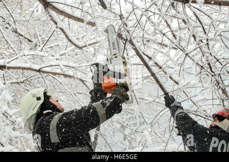 Bucharest, Romania, 17 January 2016: Firemen intervene to clear a street after a heavy snowfall in Bucharest. - Stock Photo