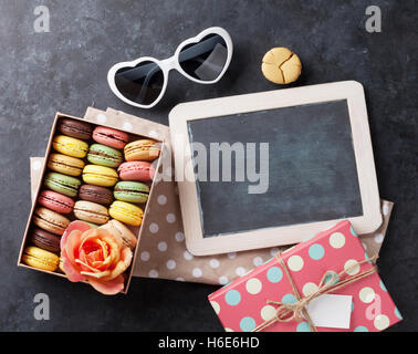 Colorful macaroons and blackboard. Sweet macarons on stone table. Top view with copy space for your text - Stock Photo