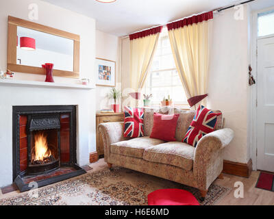 A cosy, small UK living room with roaring fire & sofa adorned with patriotic cushions - Stock Photo