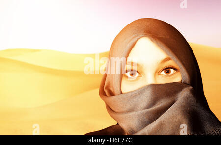 Young friendly woman with veil in the desert - Stock Photo
