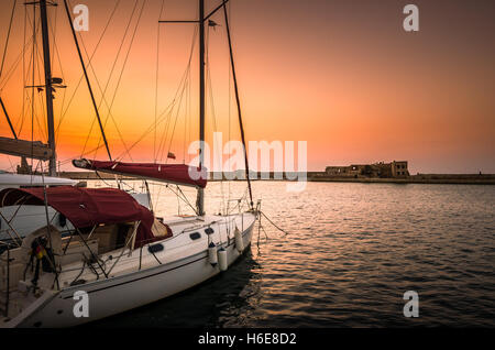 Boats in old venetian port of Chania at sunset. View of the old venetian harbor of Chania on Crete island, Greece. - Stock Photo