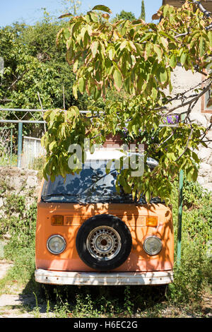 An old Vw or Volkswagen Camper van parked under a tree in a garden - Stock Photo