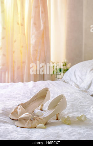 Brides sandals on the bed with wedding dress hanging in the background - Stock Photo