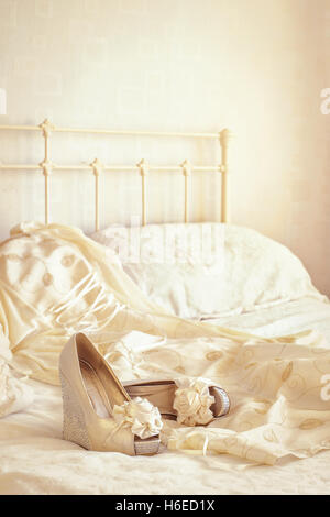 Brides wedding shoes and dress lying on the bed - Stock Photo