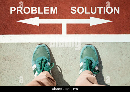 Problem or solution concept with legs from above standing on signs - Stock Photo