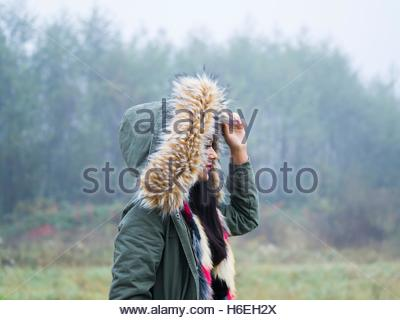 Under hood cold weather walking walk girl outdoors foggy day side view forest in nature hoodie single - Stock Photo