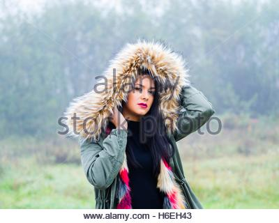 Under hood cold weather portrait cute girl outdoors foggy day waist-up isolated looking at camera eyes-contact hoodie - Stock Photo