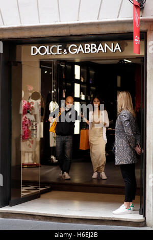 Pedestrian quit of the store with their Dolce & Gabbana shopping bag on Via del Corso, main shopping street in Rome, - Stock Photo