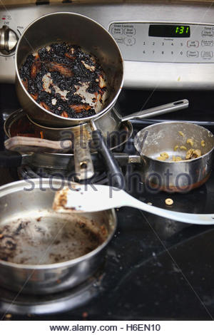 Dirty pots with caked-on old food rest on a stove-top in a messy kitchen. - Stock Photo