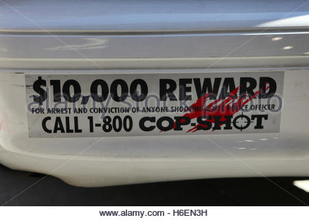 A bumper sticker on the back of a police car offering a ten thousand dollar reward for the arrest and conviction - Stock Photo