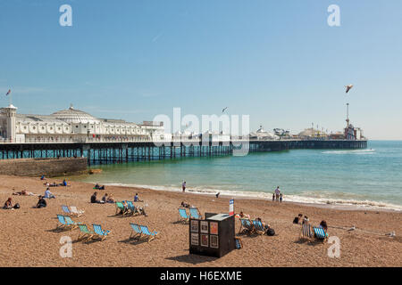Pier of Brighton, people on the beach in front - Stock Photo