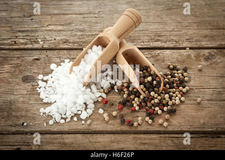 Large-grained salt and mixed peppercorns on wooden shovels, on rustic table, high angle view - Stock Photo