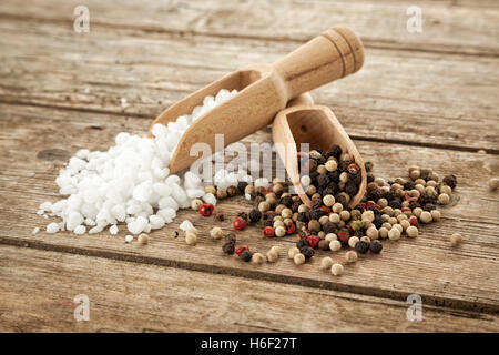 Large-grained salt and mixed peppercorns on wooden shovels, on rustic table - Stock Photo