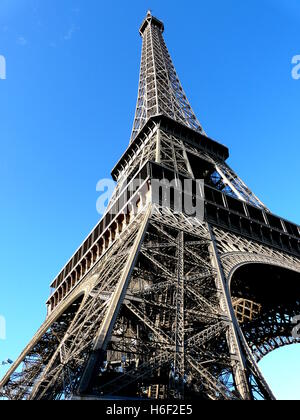 Tower Eiffel in Paris, seen from underneath one of the iron legs, on a bright blue September sky. - Stock Photo