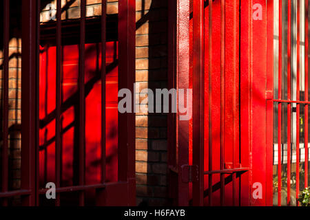 Afternoon sun giving chiaroscuro aesthetics to a brownstone structure with bright red gate, fence and entrance door. - Stock Photo
