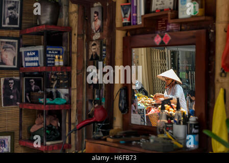 Reflection of a fruit seller on the mirror of a barber shop in a street of Hanoi. - Stock Photo