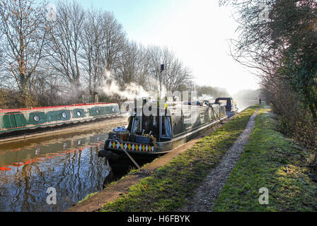 Smoke rising from narrow boats or barges on a winters day at  Norbury Junction Shropshire Union Canal  Staffordshire - Stock Photo