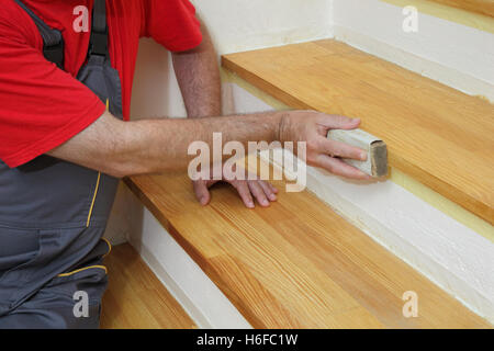 Worker sanding plank at stairs using sand paper, home renovation - Stock Photo