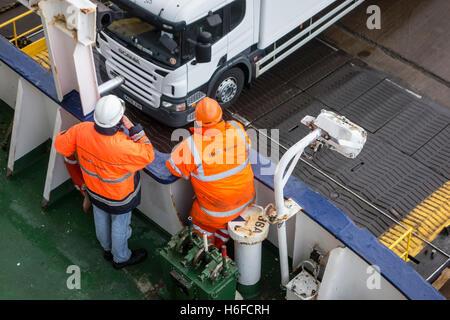 Ship's crew members in orange workwear watching trucks boarding ferry boat of P&O North Sea Ferries - Stock Photo