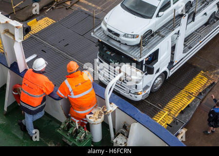 Ship's crew members watching truck with cars on car carrier trailer boarding ferry boat of P&O North Sea Ferries - Stock Photo