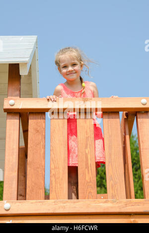 Happy little girl in a pink dress on playground - Stock Photo