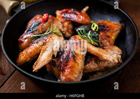 Baked chicken wings in pan on wooden table. - Stock Photo