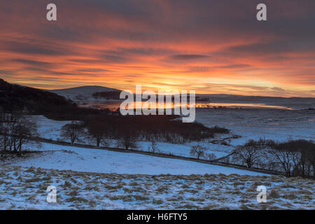 Dramatic winter sunrise over a frozen Malham Tarn in the Yorkshire Dales National Park, UK - Stock Photo