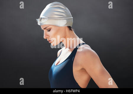Side view of fit young female swimmer on black background. Fitness woman in swimming costume concentrating. - Stock Photo