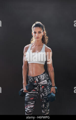 Fitness woman exercising with dumbbells. Beautiful fitness instructor on black background. Female model with muscular - Stock Photo