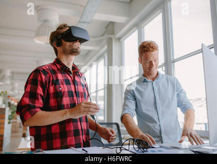 Young developer working on laptop and virtual reality glasses. Two men improving virtual reality glasses in office. - Stock Photo