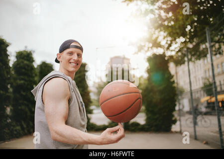Portrait of smiling streetball player spinning the ball on outdoor court. Happy young man balancing basketball on - Stock Photo