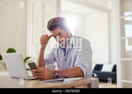Shot of serious young man using mobile phone while sitting at his work desk. Business man at table with laptop and - Stock Photo