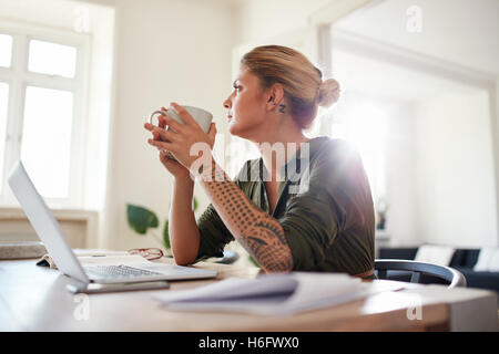 Indoor shot of young woman with coffee looking away and thinking. Thoughtful female sitting at home office. - Stock Photo
