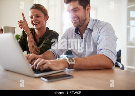 Shot of young couple at table using laptop at home. Cheerful young man and woman working on laptop. - Stock Photo