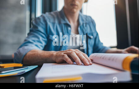 Young man reading book at library, with focus on hand. Male student studying at college library. - Stock Photo