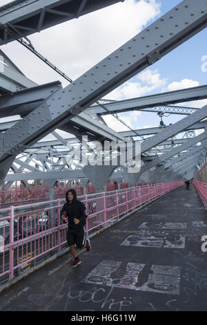 Runner headed towards Manhattan over the Williamsburg Bridge, New York City. - Stock Photo