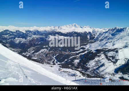 Top view of French skiing resort Meribel in 3 Valleys, with backdrop of snowy peaks of Alps, village chalets, woodland - Stock Photo