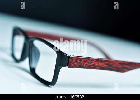 closeup of a pair of plastic and wooden rimmed eyeglasses on a white surface - Stock Photo
