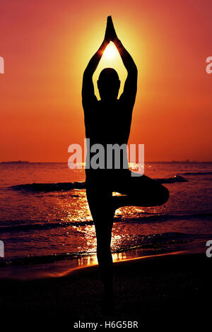 the silhouette of a young yogi man practicing the tree pose in front of the sea in backlight - Stock Photo