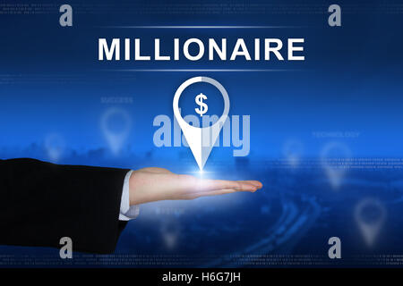 millionaire button with business hand on blurred background - Stock Photo