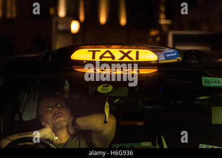 A fatigued black cab taxi driver in London's West End - Stock Photo