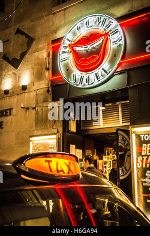Black taxi cab illuminated sign outside the Comedy Store in Soho, Central London, UK - Stock Photo