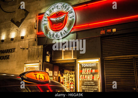 Black taxi cab sign outside the Commedy Store in Soho, Central London, UK - Stock Photo