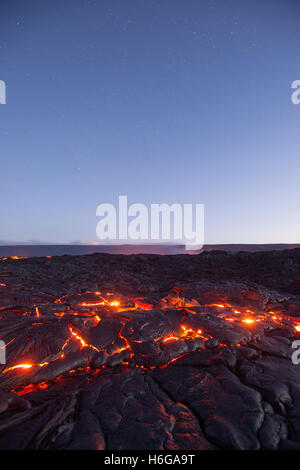 stars fill the pre-dawn sky as hot lava glows through the cracks of pahoehoe in the 61G flow, Hawaii Volcanoes National - Stock Photo