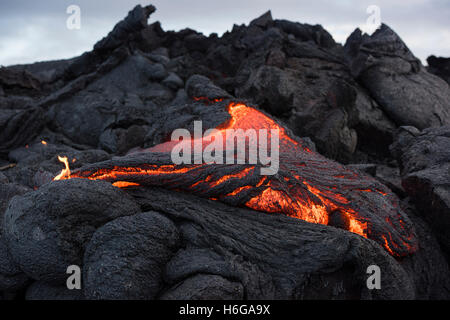 pahoehoe lava from the 61G flow, Kilauea Volcano, oozes from a breakout in Hawaii Volcanoes National Park, Hawaii, - Stock Photo