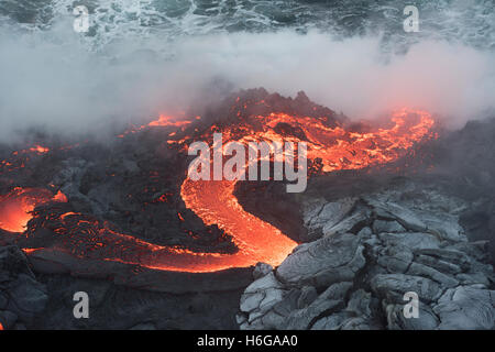 a river of hot pahoehoe lava from the 61G flow, emerges from a lava tube and pours into the ocean at the Kamokuna - Stock Photo