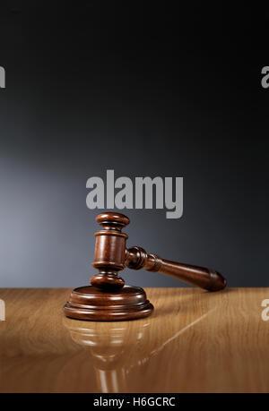 Mahogany wooden gavel on glossy wooden table. - Stock Photo